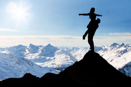 Silhouette Of Man Carrying Her Girlfriend Standing On The Top Of Snow Mountain