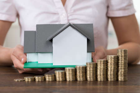 property: Close-up Of Businesswoman Holding House Model With Stack Of Coins At Desk