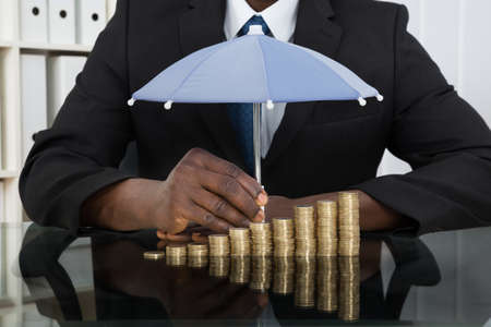 man holding money: Close-up Of Businessman Protecting Stack Of Coins With Umbrella At Desk Stock Photo