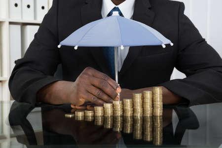 Close-up van zakenman beveiligen Stapel Muntstukken Met Paraplu Bij Bureau Stockfoto