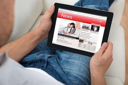 디지털 태블릿에서 뉴스를 보는 사람이 소파에 근접