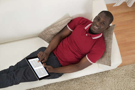 using tablet: High Angle View Of African Man Lying On Couch Holding Ebook Stock Photo