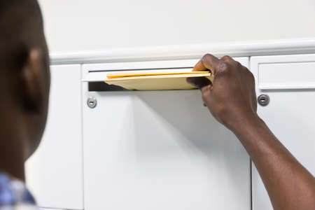 putting in: Close-up Of Person Hands Putting Envelope In Postbox