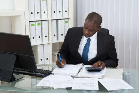 contabilidad financiera cuentas: Hombre de negocios africano joven Cálculo Finanzas Bills En Office Foto de archivo