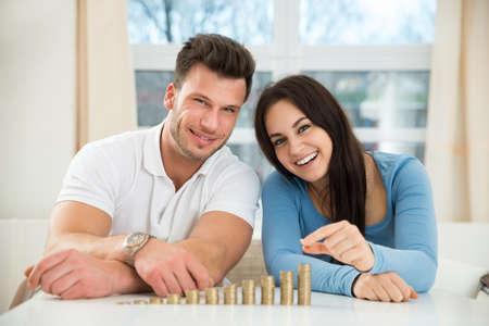 Couple heureux assis avec des piles de pièces dorées cours table à la maison Banque d'images