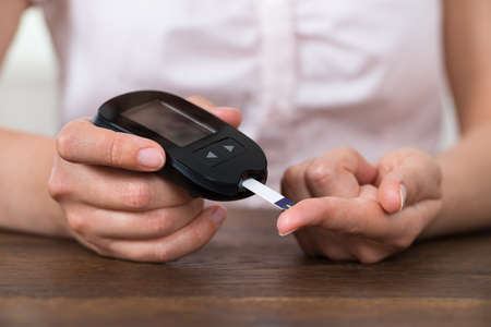 Close-up Of Person Hands Holding Glucometer At Desk