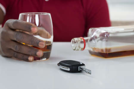 black car: Close-up Of Man Holding Glass Of Whisky With Car Key On Table
