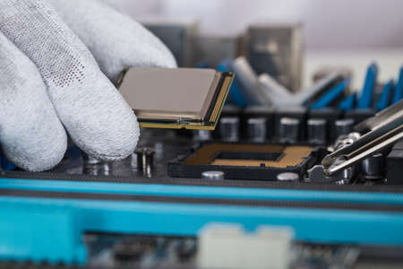 manual test equipment: Close-up Of Person Hands Installing Central Processor In Motherboard Stock Photo