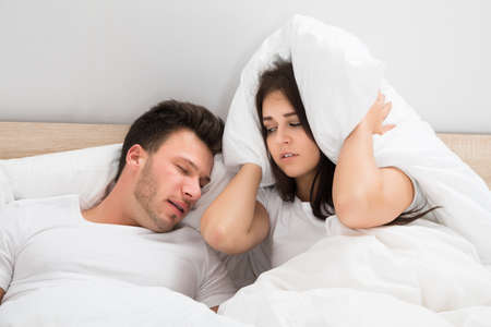 sleep: Irritated Woman Covering Her Ears With Pillow While Man Snoring On Bed At Home