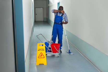 janitor: Tired Male Janitor With Cleaning Equipment And Wet Floor Sign