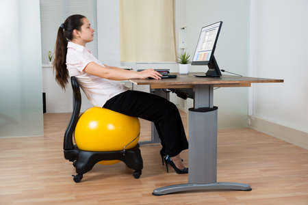 woman posture: Businesswoman Leaning On Chair With Fitness Ball While Working On Computer Stock Photo