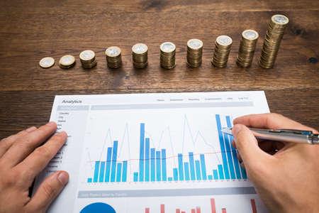 사업가 누적 된 동전의 앞에 금융 그래프를 분석