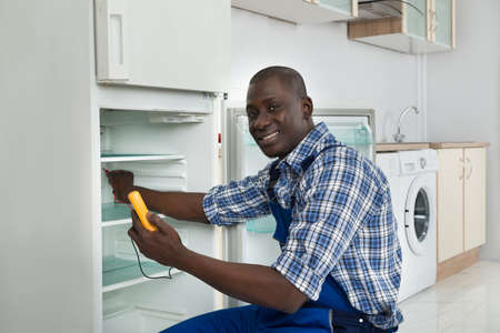 malfunction: Happy African Technician Repairing Refrigerator Appliance In Kitchen Room