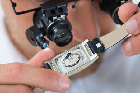 watchmaker: Close-up Of Young Man Looking Wrist Watch With Loupe