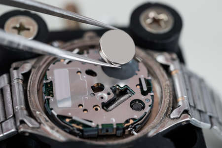 Close-up Of Tweezers Placing Battery On Silver Wrist Watch