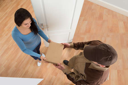 courier man: Happy Young Woman Receiving Courier From Delivery Man At Home