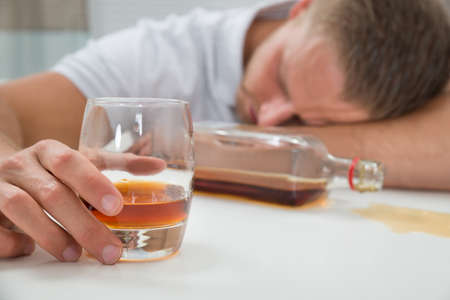 liquors: Young Drunk Man Sleeping On Table With A Glass Of Liquor Stock Photo