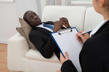 terapia psicologica: Psiquiatra Mujer Haciendo Notas En Frente De paciente durante la terapia psicol�gica Sesi�n