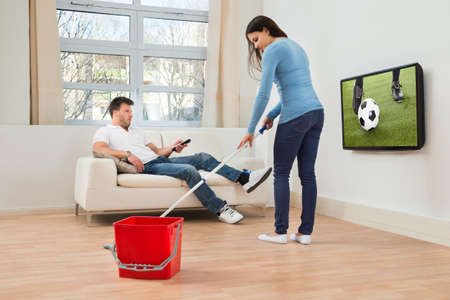 watching football: Woman Cleaning Floor In Front Of Man Watching Football Match On Television Stock Photo