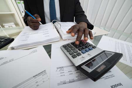 Primer plano de hombre de negocios Facturas Cálculo usando la calculadora Foto de archivo