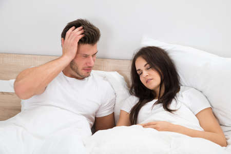 snoring: Upset Young Man Looking At Woman Snoring In Bed At Home