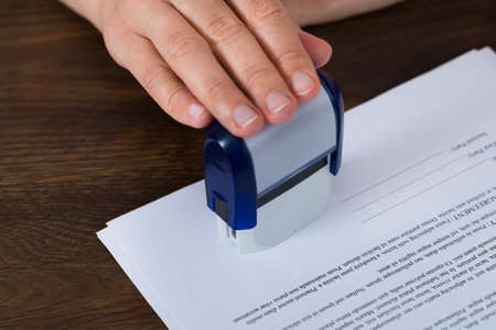 Close-up Of Person Hands Stamping Document At Desk Stockfoto