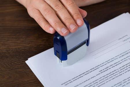 sello: Primer plano de la persona que estampa el Documento Manos En El Escritorio Foto de archivo
