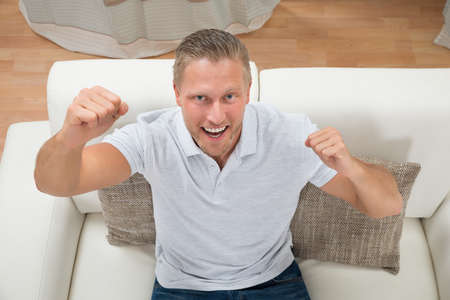 clenching fists: Portrait Of Young Excited Man Clenching Fist On Sofa Stock Photo