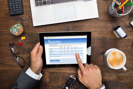 Close-up Of A Businessman Filling Online Survey Form On Digital Tablet