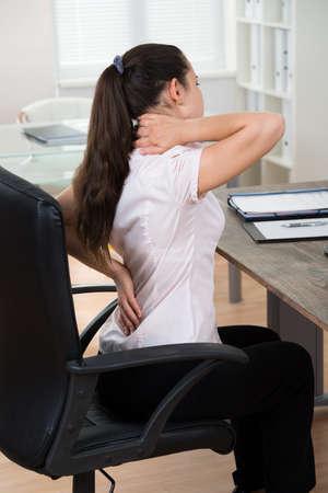 Empresaria joven que se sienta en silla Tener Backpain En Office