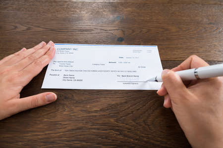 cheque: Close-up Of Person Hands Signing Cheque With Pen At Desk Stock Photo