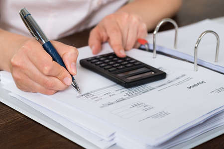 doing: Close-up Of Accountant Doing Calculation With Calculator In Office Stock Photo