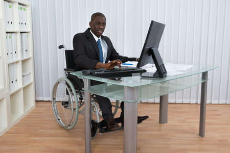wheelchair: Portrait Of Happy African Businessman Working In Office Sitting On Wheelchair
