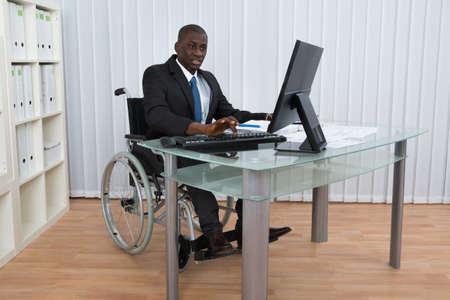 personas discapacitadas: Retrato de feliz hombre de negocios de África en Oficina sentado en silla de ruedas Foto de archivo