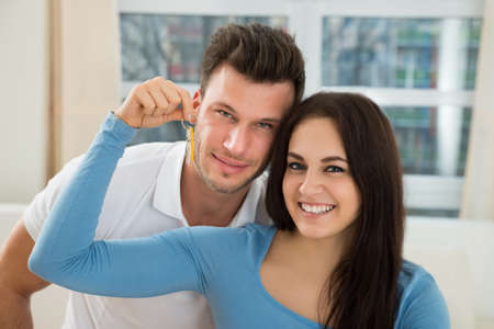 condos: Portrait Of Happy Young Couple Holding Keys