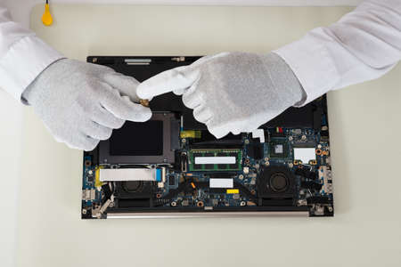 repairer: Close-up Of Technician Repairing Laptop At Desk