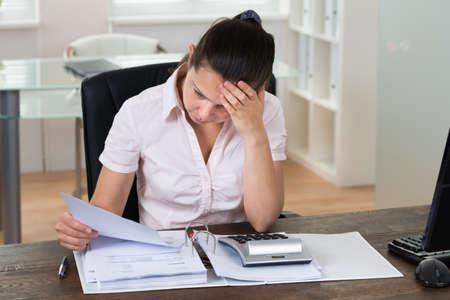 factura: Joven tensionada Comprobación de Cuentas en la oficina Foto de archivo