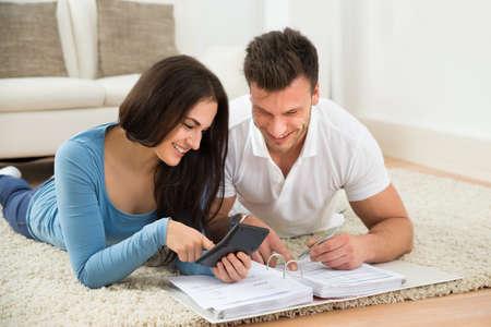 請求書を計算する敷物の上に横たわる、幸せな若いカップルの肖像画 写真素材