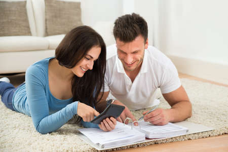 family budget: Portrait Of A Happy Young Couple Lying On Rug Calculating Invoice