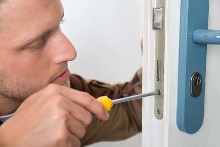 menuisier: Portrait Jeune Homme Carpenter Réparation de verrouillage de porte