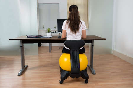 sitting at desk: Young Businesswoman Sitting On Fitness Ball While Working On Computer In Office