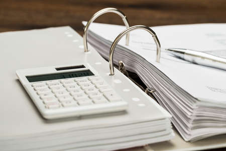 remit: Close-up Of Invoice With Calculator And Pen On Desk