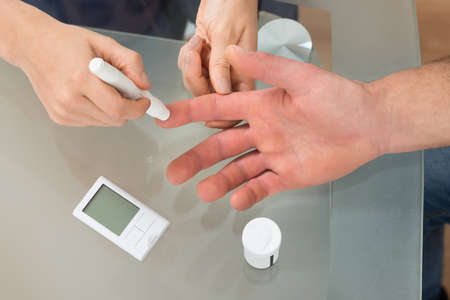 blood sugar level: Close-up Of Female Doctor Using Lancelet On Man At Desk In Clinic