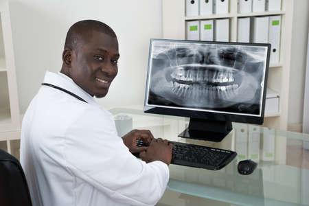 monitor de computadora: Joven dentista africana feliz con rayos X Dientes En El Ordenador En El Escritorio Foto de archivo