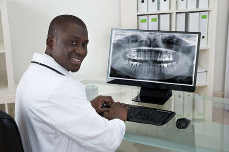 looking at computer screen: Young Happy African Dentist With Teeth X-ray On Computer At Desk Stock Photo