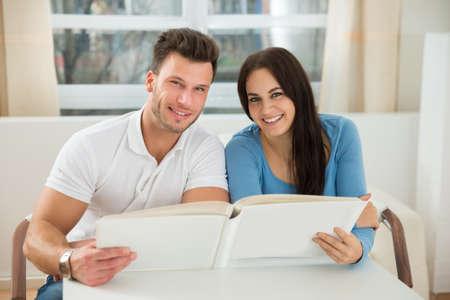 indoor photo: Portrait Of Happy Couple Holding Photo Album At Home