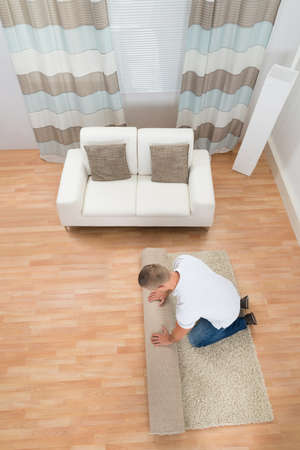 domesticity: Young Man Unrolling Carpet In Living Room