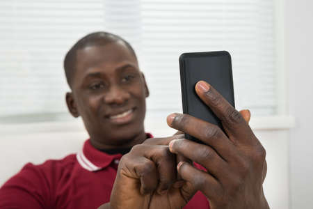 afro man: Close-up Of Smiling Young African Man Taking Selfie On Cellphone