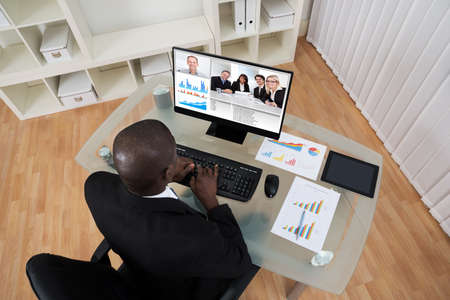 conferencing: High Angle View Of Businessman Video Conferencing With Colleague On Computer In Office
