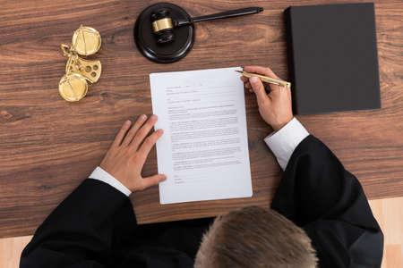 Close-up van mannelijke rechter het lezen van papier in rechtszaal